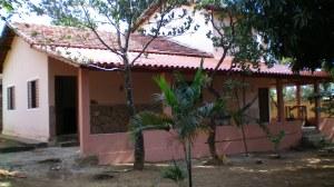 Cercada por mangueiras, jaqueiras, tamarindeiros e outras árvores de grande porte, no verão ela não difere muito das outras casas.