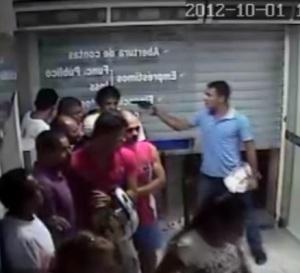Impunemente o assaltante aponta uma arma para a cabeça de uma pessoa desprevenida.